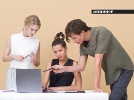To kvinder og en mand kigger på en laptop